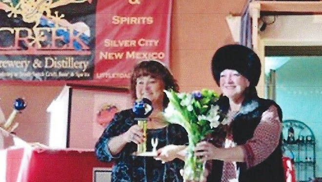 Cheryl Howell of Las Cruces, at left, accepts a bouquet from presenter Ramona Maltby at Silver City's Annual Chocolate Fantasia on Feb. 6.