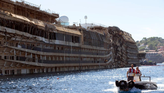 People take a small boat past the damaged side of the Costa Concordia  on the Tuscan Island of Giglio, Italy, on Sept. 18, 2013.