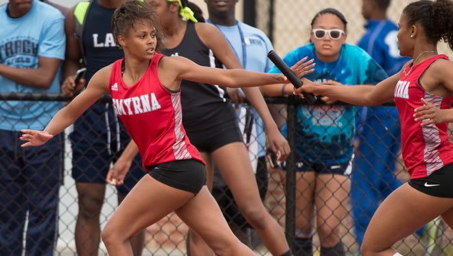 Smyrna's Lauren Summers receiving the baton from Shaneese La Mons during the division 1 girls 4x200 meter relay race at the DIAA State Track & Field Championships at Dover High School.