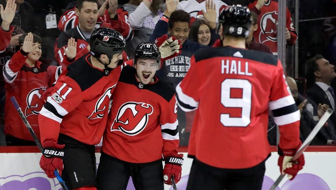New Jersey Devils defenseman Will Butcher, center, Brian Boyle, left, and left wing Taylor Hall (9) celebrate Boyle's goal during the second period of an NHL hockey game against the Vancouver Canucks, Friday, Nov. 24, 2017, in Newark. Butcher and Hall assisted Boyle on the goal.