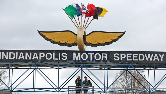 FILE -- WNBA Indiana Fever player Tamika Catchings, left, and IMS's Stephen Woods come down after placing racing flags at the Indianapolis Motor Speedway, Friday, March 27, 2015.  To mark the start of the 2015 Verizon IndyCar Series season and serve as a reminder that the second annual Angie's List Grand Prix of Indianapolis and the 99th Indianapolis 500 are around the corner, the racing flags were placed atop the famous Wing and Wheel logo above the Indianapolis Motor Speedway's Gate 1.
