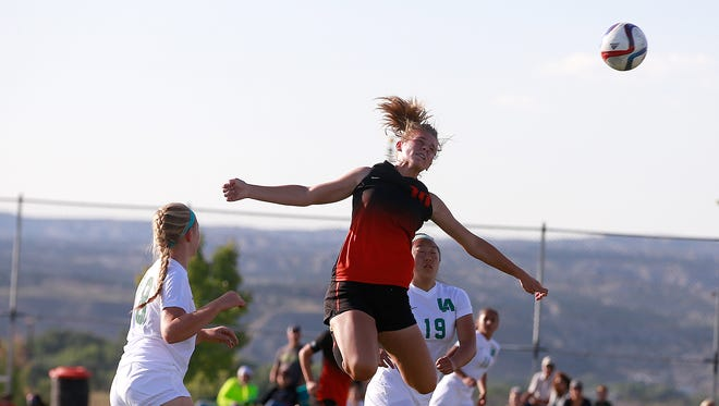 Aztec's Autumn Roundy heads the ball against Los Alamos on Aug. 20 at the Aztec Tiger Sports Complex.