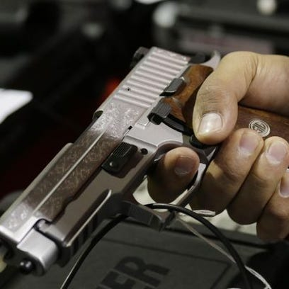 A customer looks at a SIG Sauer hand gun at a gun show