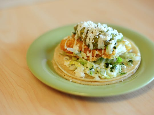 The fish taco is served with breaded fish topped with cabbage, queso fresco, lime and salsa.