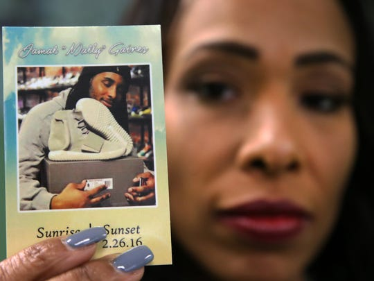 "Tina Wilson holds a photo of her son, Jamal ""Mally"" Gaines, 21, the owner of East Coast Boutique, a sneaker store at 1546 Irving St. in Rahway. Gaines was shot outside the store last year and died at the scene."