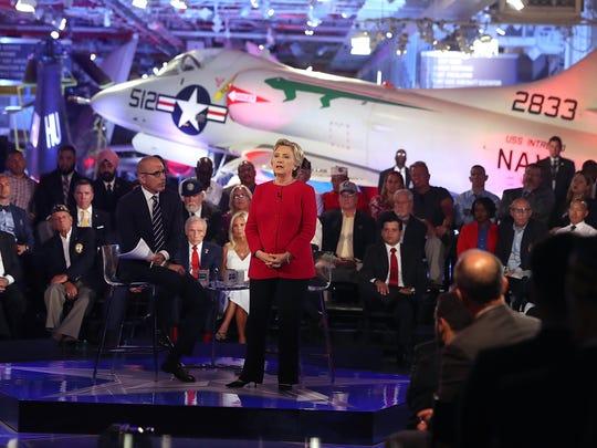 Matt Lauer looks on as Hillary Clinton speaks during