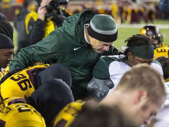 MSU coach Mark Dantonio prays with Minnesota players after the Spartans' win there on Thanksgiving weekend 2012. Dantonio keeps the stocking cap he wore that day in his office, considering this win among the most important of his tenure.