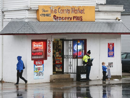 """Ronnie Gathof, wearing yellow jacket, waits outside """"The Corner Market"""" to pick up his stepson after school in the Portland neighborhood.Nov. 28, 2016"""