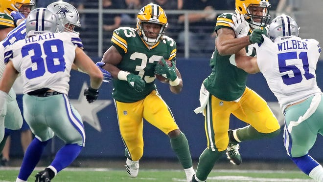 Green Bay Packers running back Aaron Jones (33) bursts through a hole as tight end Lance Kendricks (right) blocks against the Dallas Cowboys on Sunday.