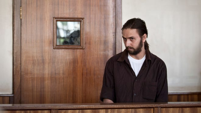In this photo taken Monday, Dec. 22, 2014, American Ryan Gustafson faces charges of forging currency, at a magistrates court in central Kampala, Uganda. Gustafson faces 25 years in prison if convicted of the charges that came after his arrest in the East African country early this month, and will remain jailed until the continuation of his trial on Jan. 9, 2015, according to the chief magistrate.