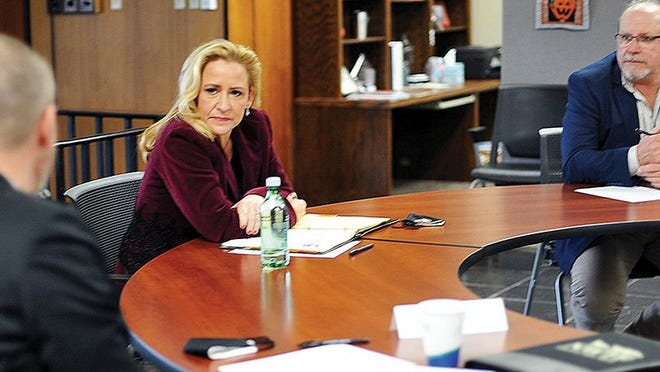 Attorney General Leslie Rutledge listens to Garland County Undersheriff Jason Lawrence last Tuesday. Listening at right is Garland County Judge Darryl Mahoney.