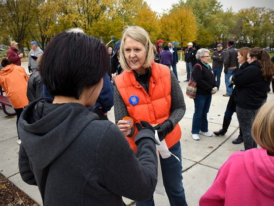 Janet Reagan passes out stickers during a rally in