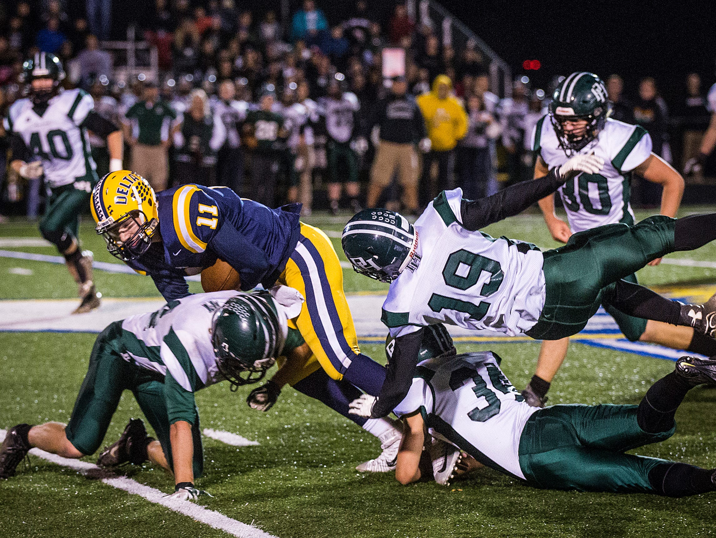 Delta's Ryley Pease fights for yards against Pendleton Heights's defense during their game at Delta High School Friday, Nov. 6, 2015.