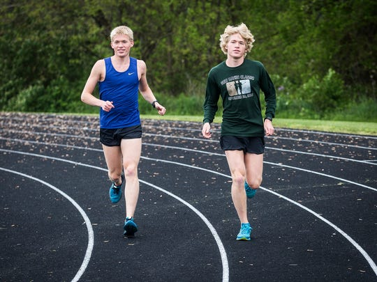 Wapahani's Alex and Nathan Herbst run on the track during a practice at Wapahani High School Thursday, May 11, 2017.
