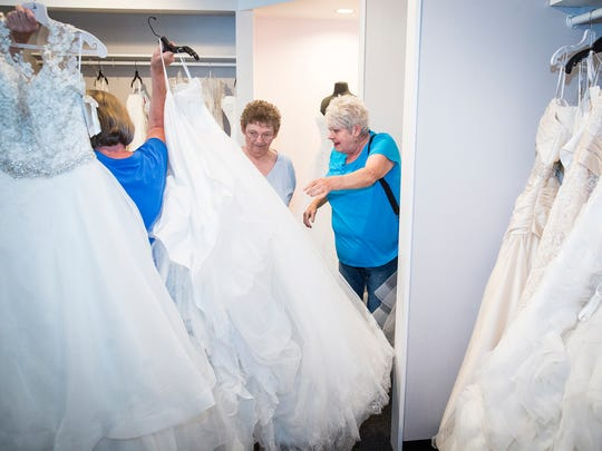 "Sherry Woodard and her sister, Carla Gick, pick out wedding dresses for Sherry to try on at Saturday's Bridal Shop in Muncie. Gick, has been planning a ""Say Yes to the Dress""-themed ""Sweet 70th"" birthday party for Woodard who has special needs and watches the TV show regularly"