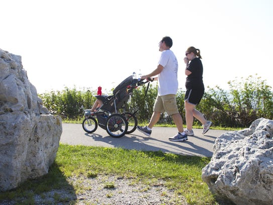 A family walks on the Mariner's Trail between Manitowoc