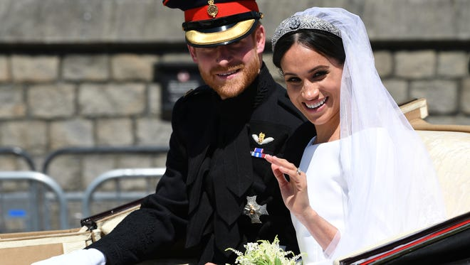 Britain's Prince Harry, Duke of Sussex and his wife Meghan Markle, Duchess of Sussex wave from the Ascot Landau Carriage during their carriage procession on Castle Hill outside Windsor Castle in Windsor, England after their wedding ceremony Saturday, May 19, 2018. (Paul Ellis/pool photo via AP)