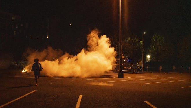 A man runs out of the smoke of a chemical munitions deployed by the Eugene police in a University of Oregon parking lot on 14th Avenue and Alder Street on Sunday night. [Dana Sparks/The Register-Guard] - registerguard.com