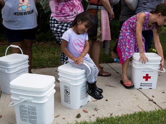 Ailin Guadalupe Garcia, 3, rests on a donation box given out by the American Red Cross as her family waits in line to receive water and food at New Hope Ministries Wednesday, September 20, 2017 in East Naples.
