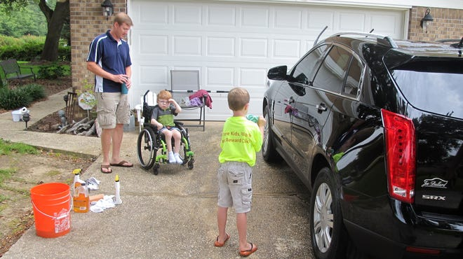 Sterling Murset washes a car at the home of Todd Blanchieri, left, in Pensacola, Fla. The Murset family is touring the country doing chores for families in need like the Blanchieri family.