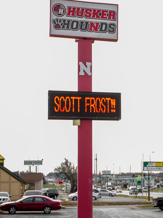 "A scrolling sign outside the Husker Hounds athletic merchandise store in Omaha, Neb., reads ""Come Home Scott Frost"", Tuesday, Nov. 28, 2017. Nebraska fans are gearing up for what they hope is the imminent arrival of Scott Frost as the Cornhuskers' new football coach. T-shirts imploring Frost to ""Make Nebraska Great Again"" are popular, and bars around town are setting drinks on ""Hire Scott Frost Now!"" coasters. (AP Photo/Nati Harnik)"