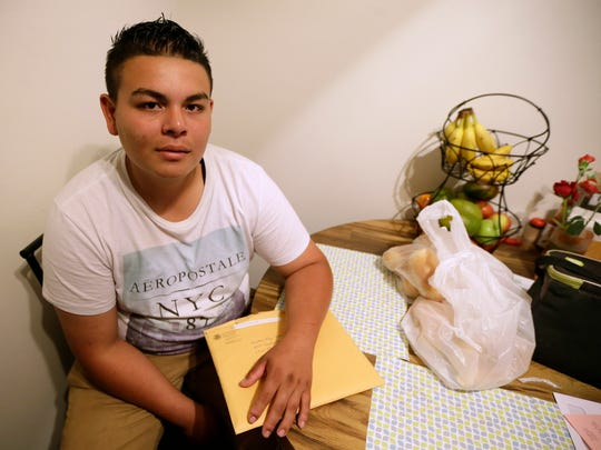 Jonathan Lopez, of Des Moines, Iowa, holds an envelope