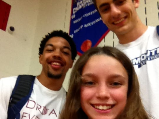 Monmouth University basketball  fan Erica Schaeffer takes a selfie after a Jersey Shore Summer League game with Hawks' players Justin Robinson (left) and Louie Pillari.