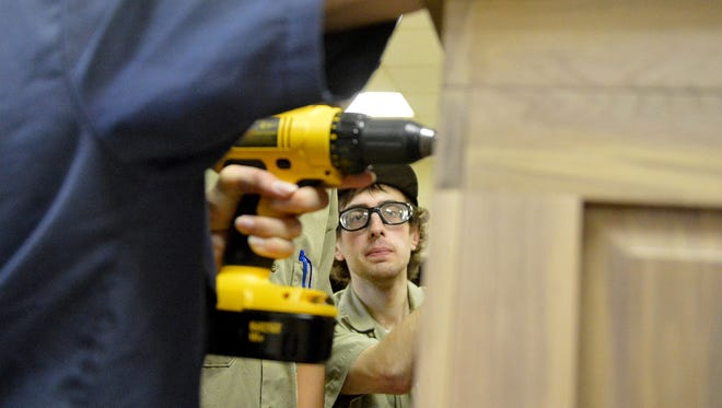 A student in the building trades program, Christopher Anderson helps fasten the top in place on a hope chest he creates with other students in the cabinetmaking and carpentry shop at Woodrow Wilson Rehabilitation Center in Fishersville on Thursday, July 24, 2014.