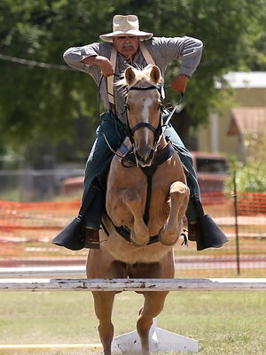 Rick Dill holds on tight as his horse jumps over an obstacle during the U.S. Cavalry Association's regional competition at Fort Concho on Thursday, April 21.