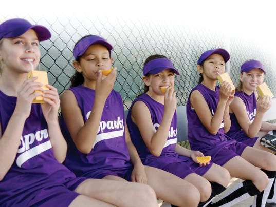 Little league players drinking juice boxes and eating oranges