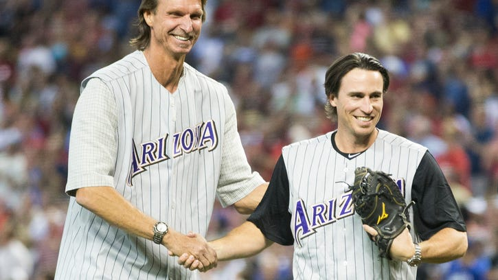 Former Diamondbacks pitcher Randy Johnson shakes hands with former catcher Robby Hammock after throwing out the first pitch before Sunday's game against the Dodgers at Chase Field in Phoenix, Ariz. May 18, 2014. Johnson was honored before the game on the 10-year anniversary of his perfect game against the Braves. The left-handed pitching legend is asking $25 million for the 25,000-square-foot Tuscan-style home near Mummy Mountain.