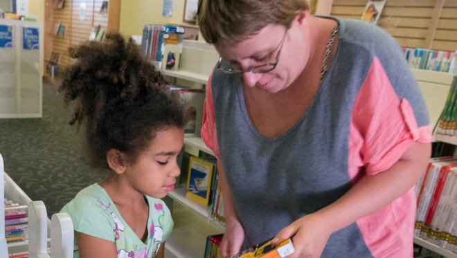 In this 2015 file photo, Elizabeth Dell, right, of York, picks out books with her daughter Mariah, then 7, at Martin Library.