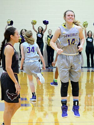 Hardin-Simmons' Danie Mabry jumps in celebration while McMurry's Isabel Carrion leaves the court after the Cowgirls' 51-50 win Saturday at the Mabee Complex.