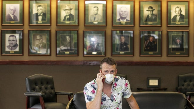 Portraits of former Marion County sheriffs line the wall behind Jeff Kershner as he sits in the lobby of the Marion County Sheriff's Office on Thursday. Sheriff Billy Woods eased his no-mask policy, now allowing visitors to wear masks after briefly removing them so security cameras can capture their face. On Tuesday, Woods announced that all sheriff's employees, with some exceptions, would not wear masks. The move drew national attention.