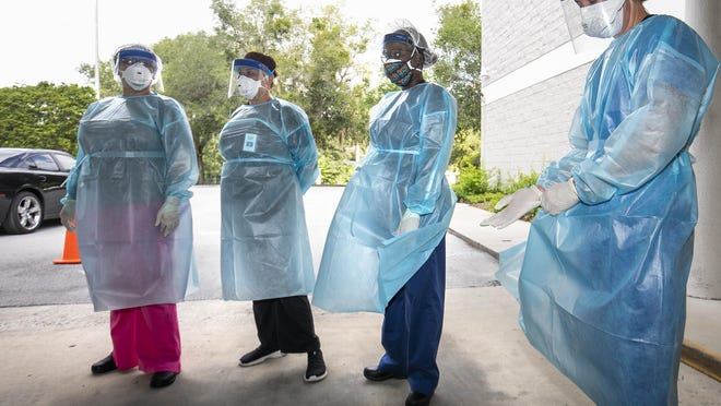 A nurse puts on fresh gloves, right, as other nurses wait to be sent to a vehicle while protected in a gown, mask, gloves and a face shield at the Florida Department of Health in Marion County on July 2.