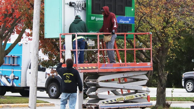 These workers from Mid-Illinois Electric were working on the sign in front of Trainor's BP on Howard Street Friday morning.