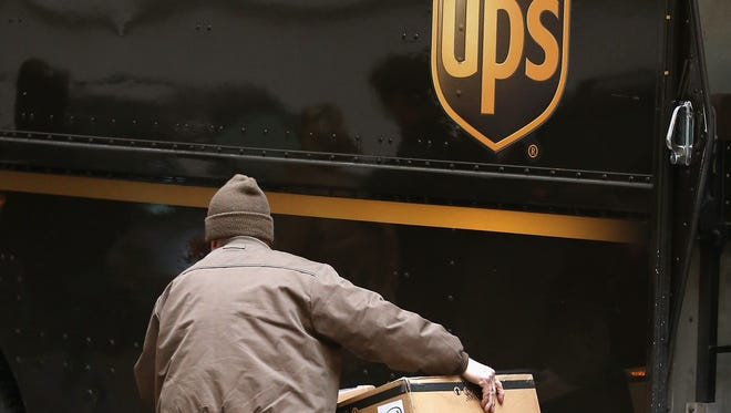 A UPS worker makes deliveries Friday in Chicago.