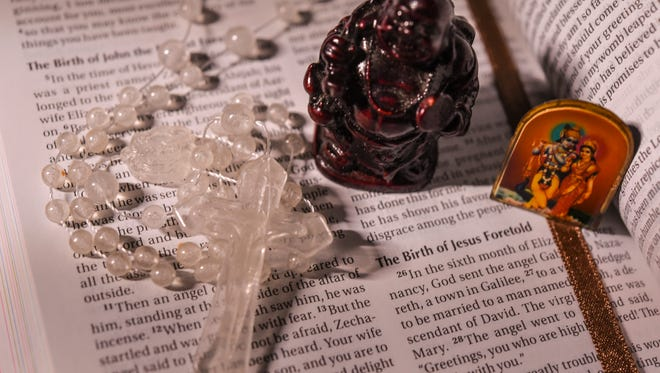 From left, Catholic rosary, Buddha figurine and a Hindu Krishna pendant photographed  on a holy bible in Hagåtña on May 4, 2017.