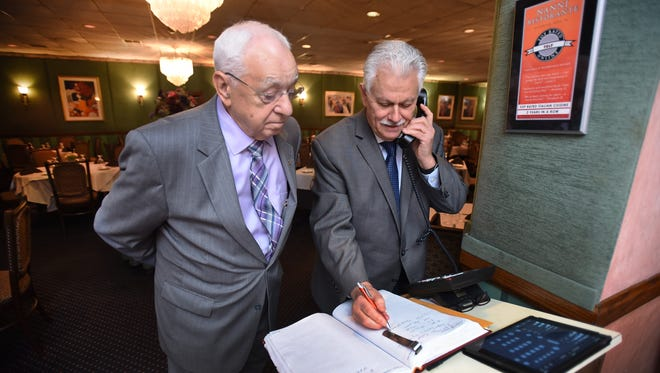 Owners of Nanni Ristorante in Rochelle Park, Manny Moreira (R) takes a call as Lino Queirolo (L) looks on at the reception desk on 10/17/18.