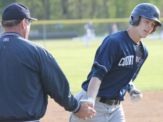 Senior Austin Richey low-fives coach Tim Dunn while rounding the bases after his grand slam against Summit April 30.