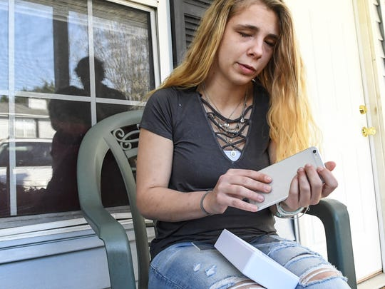 Kaylee Muthart of Anderson sits on her home front porch, unpacking an iPhone 6 plus with features that will help her use the phone.