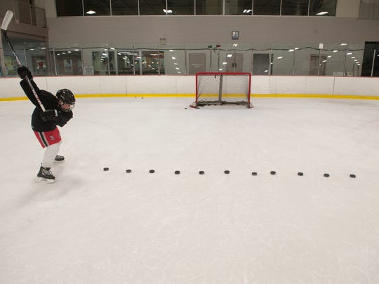 Youth player Steve Kanakaris, shoots the puck during a practice drill at the Hollydell Ice Rink in Sewell.