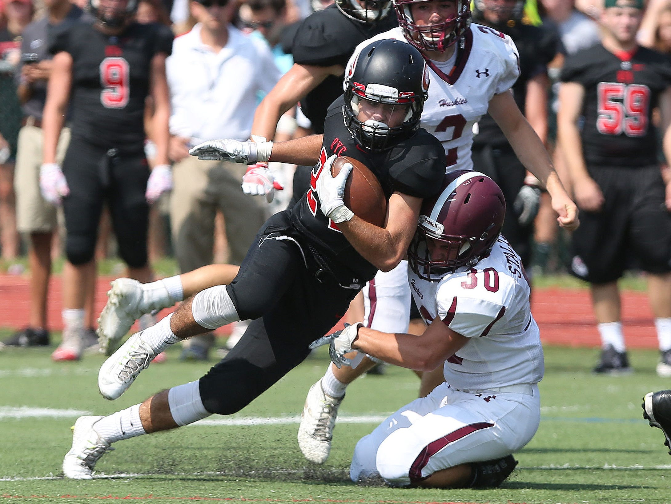 Rye's James Chabot (24) tries to get around Harrison's Kyle Stalteri (30) during first half action in the annual rivalry game at Nugent Stadium at Rye High School Sept. 10, 2016. Rye won the game 42-12.