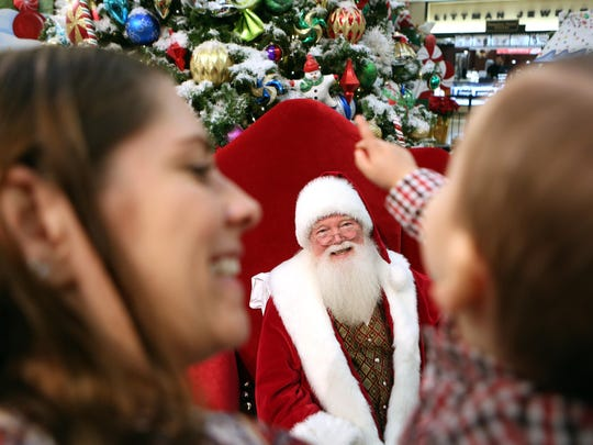 """Jace Jurik, 15 months, of Manahawkin, points to the Christmas tree as Santa says hello. The Santa Claus at the Ocean County Mall has been there for about a decade. We will discuss with """"Santa"""" why he keeps coming back to Ocean County year after year, how the children have changed, what are the strangest requests he has received from children, do some kids really lose control of their bladder as the immortalized in the movie classic """"A Christmas Story,"""" and what does Santa do to prevent children from pulling on his whiskers. Toms River, New Jersey. Saturday, January 24, 2015. David Gard /Correspondent"""