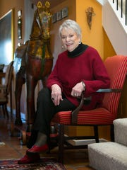 Peg Tigue.wears a black turtleneck sweater; Margaret Winters red and black sweater with back pocket; and black slacks by Clara SunWoo.