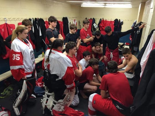 "Port Huron's hockey team gathers around a DVD player to watch an emotional video message from Mike ""Doc"" Emrick before the Larry Manz Tournament."