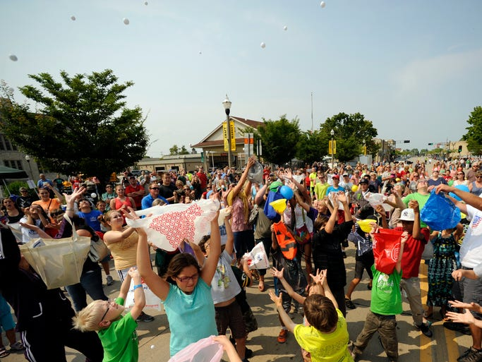 Hundreds reach out for falling ping pong balls during the annual Maxwell Street Days event on Friday, Aug. 1, 2014 along Washington Street in Two Rivers. Matthew Apgar/HTR Media