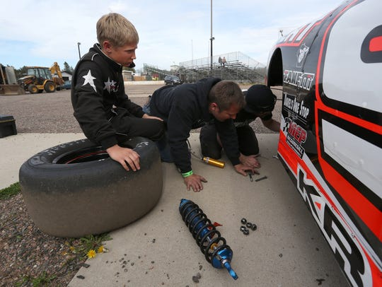 Derek Kraus, left, sits on a tire as he watches his