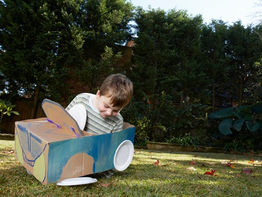 Boy playing with car made from cardboard box and plates