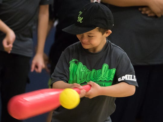 Miracles Baseball player Emiliano Gomez is all smiles as he hits the ball during the Dream League baseball game at Meersheidt Recreation Center on Saturday.